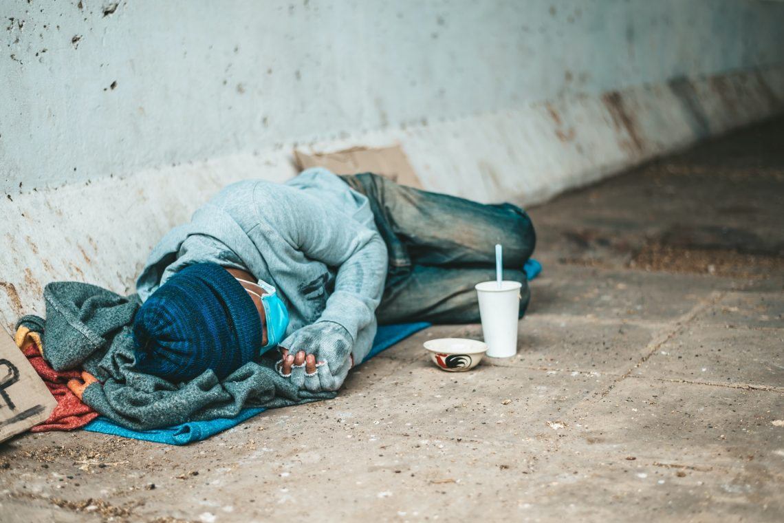 Beggars lying on the side of the street with dirty clothes.